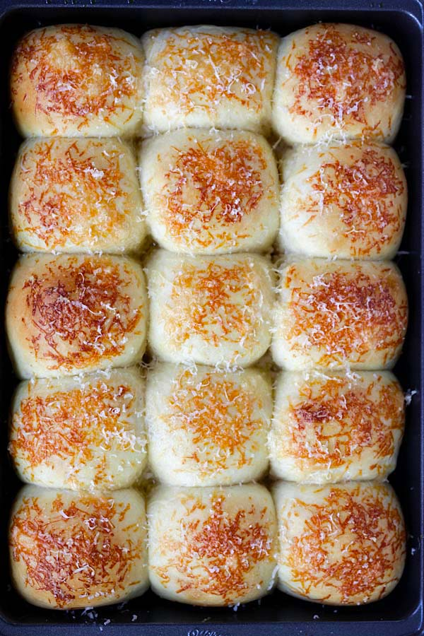 Delicious, easy and healthy homemade cheesy Parker House Rolls with Parmesan cheese in a baking tray.