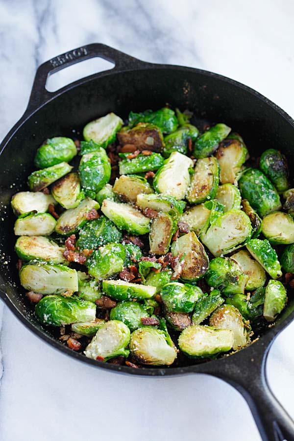 Easy and healthy homemade skillet roasted Brussels sprouts with garlic, Parmesan cheese and bacon.