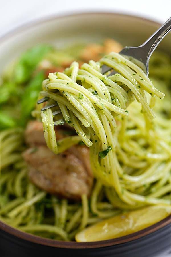 Pesto spaghetti pasta twirled on a fork.