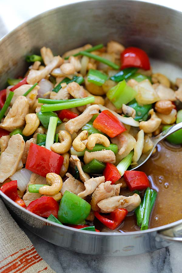 Thai stir-fry cashew nuts chicken with bell peppers, in brown Asian sauce in a skillet.