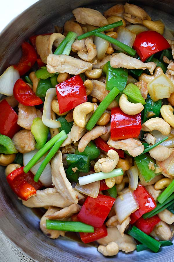 Top down view of tasty Thai stir-fry cashew chicken in brown sauce cooked with bell peppers, onions and scallions.