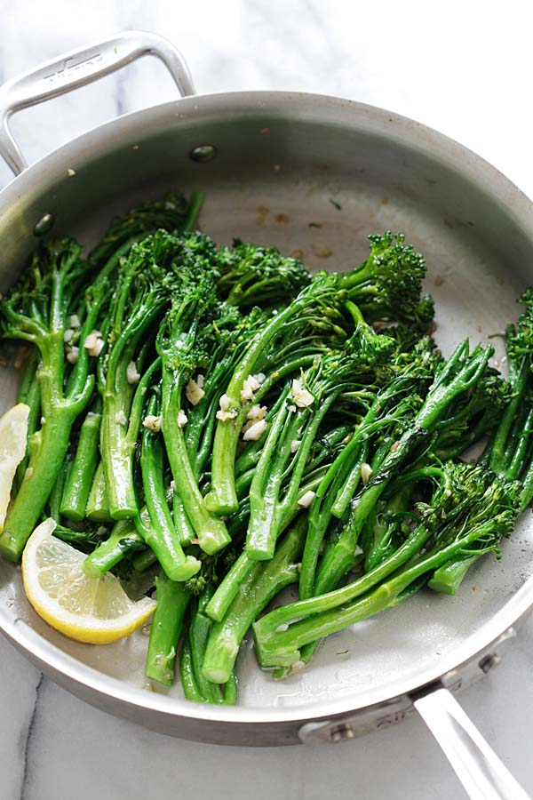 Broccolini sauteed with garlic butter cooked in a pan.