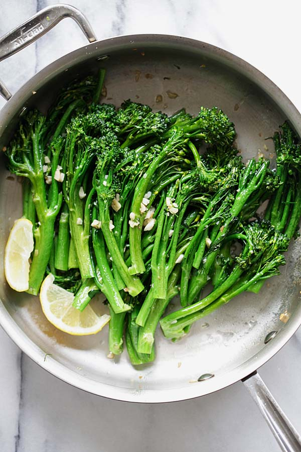 Top down picture of garlic butter sauteed broccolini in a skillet.