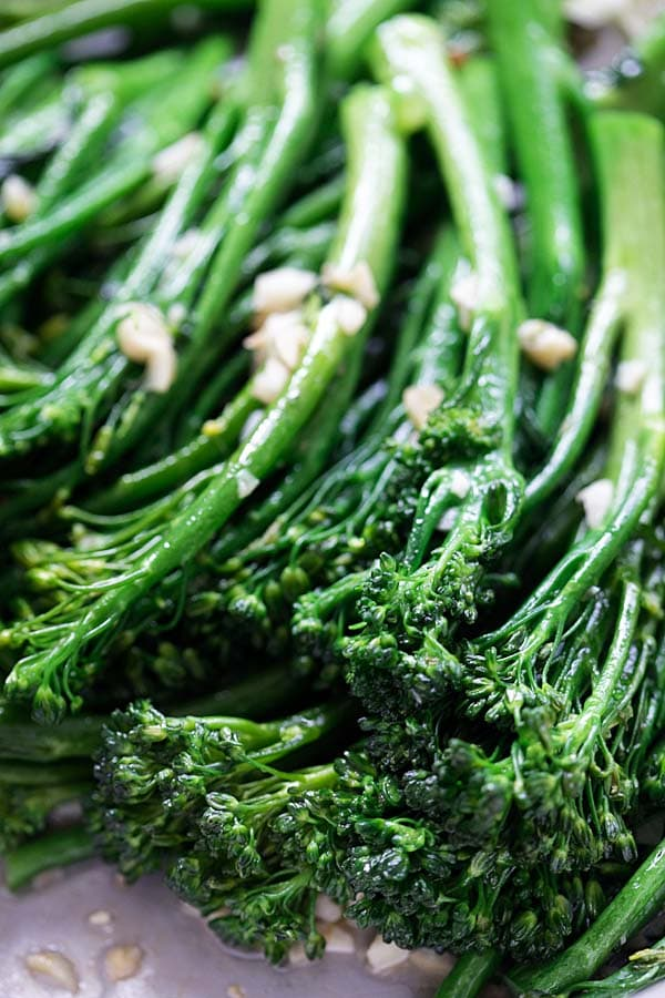 Close up of broccolini with garlic and other ingredients.