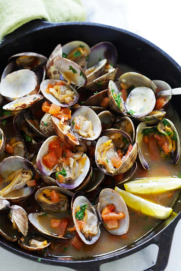 Italian sauteed clams with lemon and tomatoes, in a skillet.
