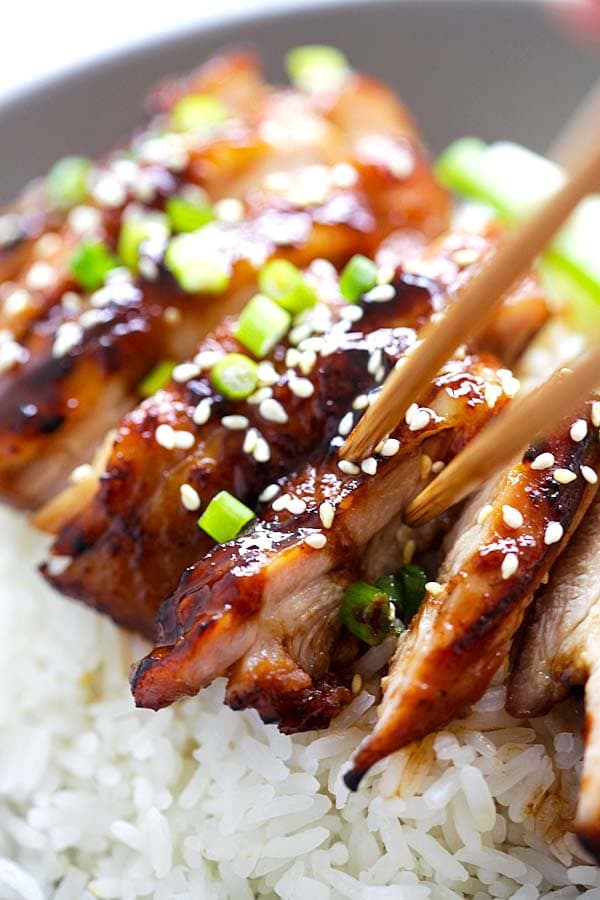 Tasty soy-glazed chicken on top of steamed rice garnished with chopped scallions and sesame seeds, ready to serve.
