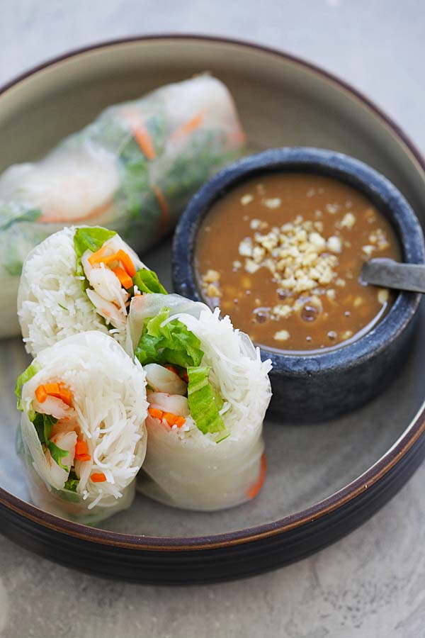 Easy and quick authentic Vietnamese summer rolls wraps, cut into half and served in a plate with a side of hoisin peanut sauce.