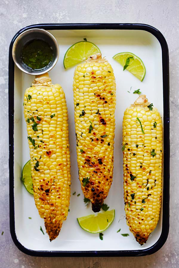 Top down view of buttery grilled corn marinade with honey, cilantro and lime juice.