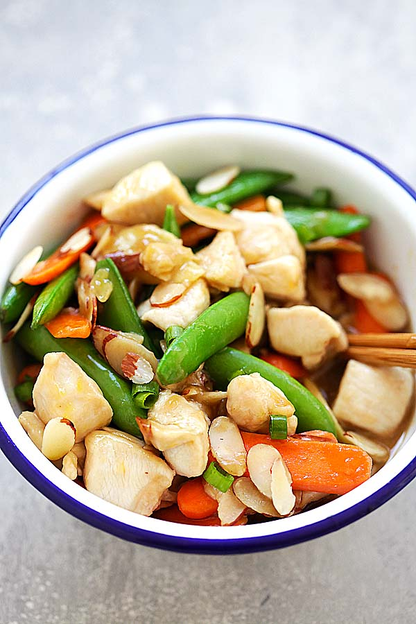 Easy and healthy chicken stir-fry with almonds, peas and carrots in Chinese brown sauce, served in a metal bowl.
