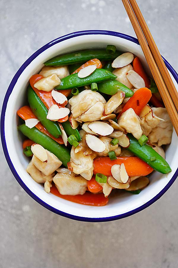 Stir fry Almond nuts with chicken breasts in Chinese brown sauce, in a metal bowl.