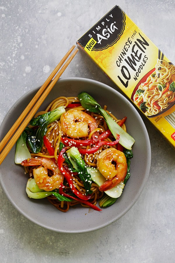 Lo mein in a bowl covered in shrimp and vegetables, next to a box of the lo mein noodles from McCormick Simply Asia.