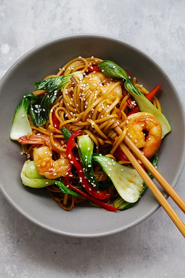 Lo mein noodles with shrimp being picked up by a chopstick.