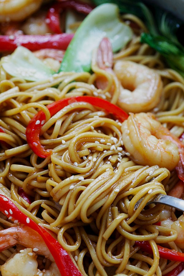 Closeup of the lo mein noodles with shrimp on a fork with some sesame seeds on it. Super saucy and delicious.