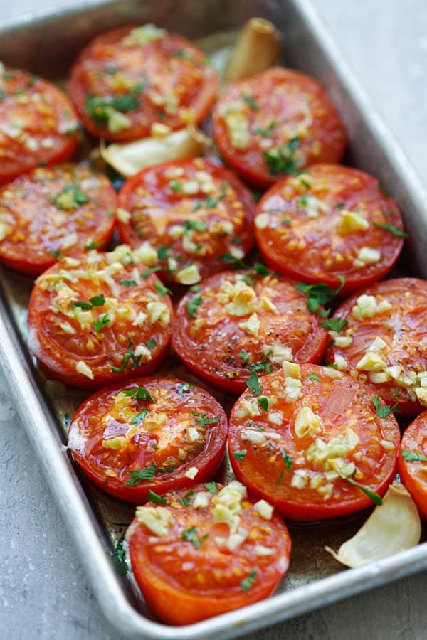 Juicy slow oven Roasted Tomatoes with garlic sauce in a baking tray.