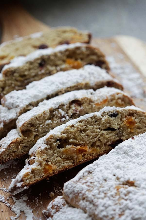 Easy Pecan and dried fruits Holiday Bread sliced on a wooden chopping board.