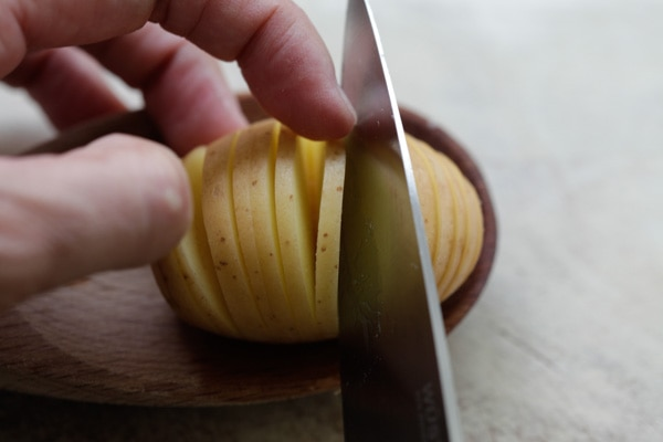 Cutting Hasselback potatoes with a knife.