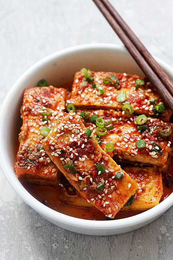 Homemade healthy and delicious spicy Korean Tofu Banchan in a bowl with a pair of wooden chopsticks.