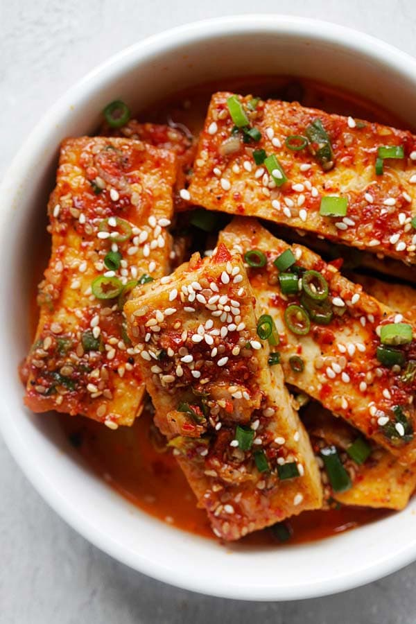Korean braised tofu topped with sesame seeds and chopped scallion (side dish) in a bowl ready to serve.