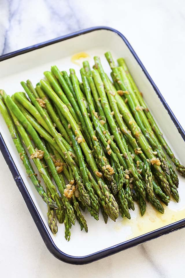 Garlic butter sauteed asparagus in a white serving ware.