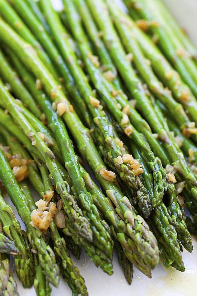 Close up picture of sauteed asparagus with butter and minced garlic.