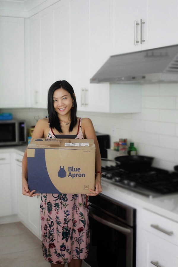 Bee holding a Blue Apron box.