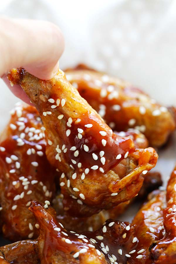 Sweet and Sour baked crispy chicken wings picked with fingers.