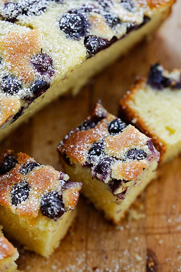 Butter cake with blueberries on top, cut into bite-sized pieces.