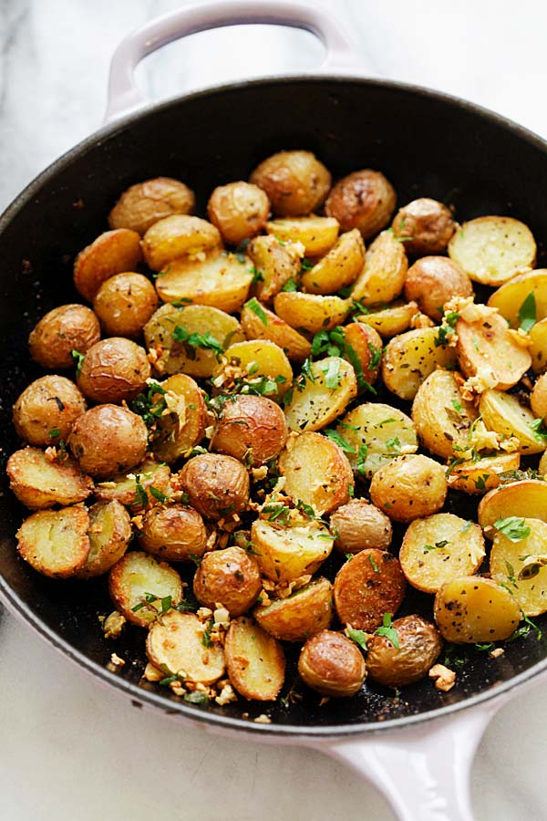 Crispy Roasted Potatoes with garlic herb infused oil in a skillet.