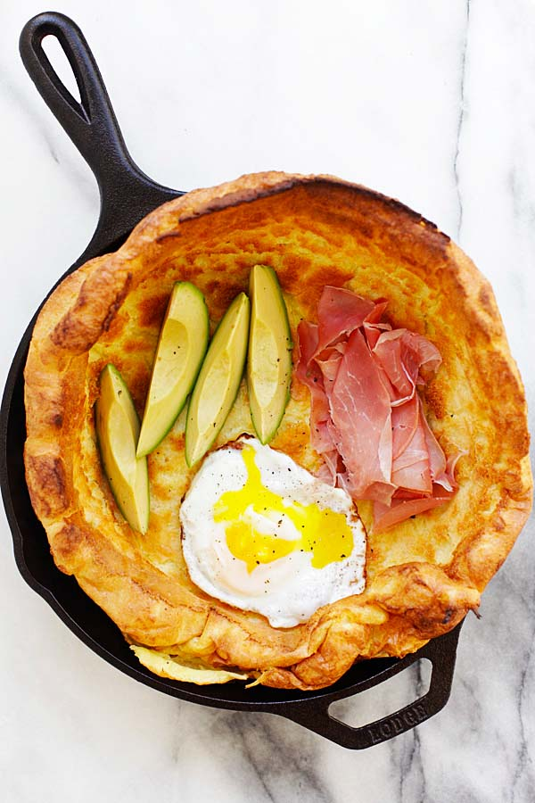 Easy brunch Dutch Baby with egg, prosciutto and avocado in a skillet.