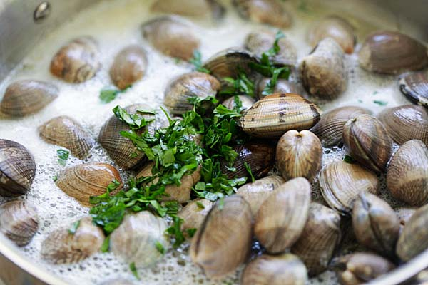 Adding beer into a skillet of steamed clams.
