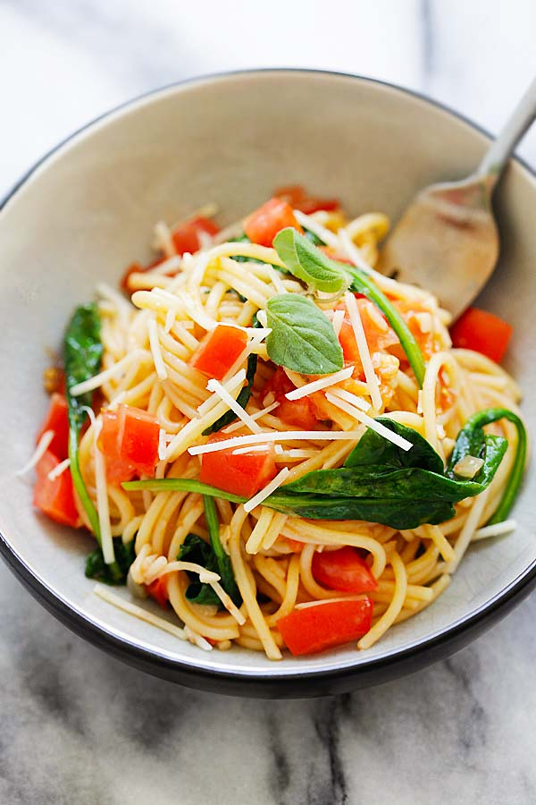 Easy and quick one-pot spaghetti pasta with spinach and tomatoes serve in a plate.