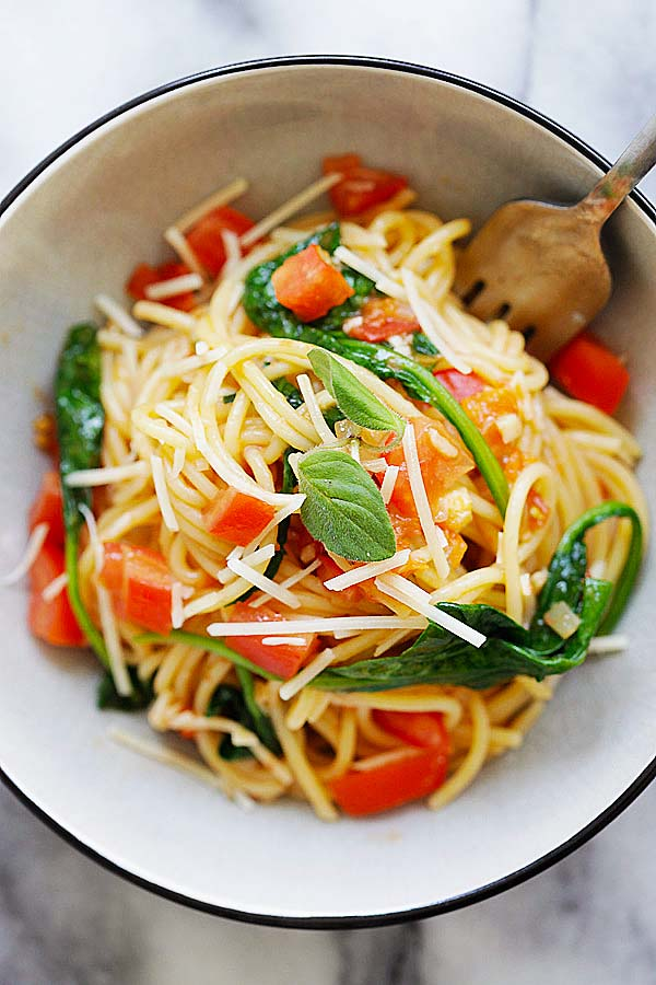 Healthy and delicious spinach and tomatoes pasta in served in a pasta bowl.