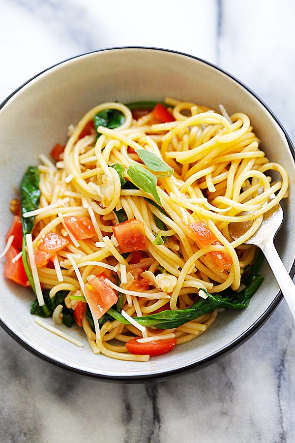 Close up of pasta with spinach and tomatoes.