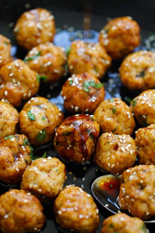 Teriyaki chicken meatballs marinade with Japanese teriyaki sauce in a skillet.