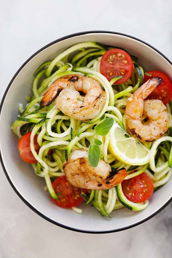 Top down view of zucchini noodle salad with lemon-honey dressing in a bowl.