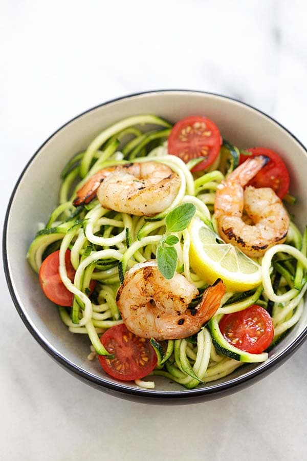 Healthy homemade zucchini noodle salad topped with grilled shrimp and lemon-honey dressing.