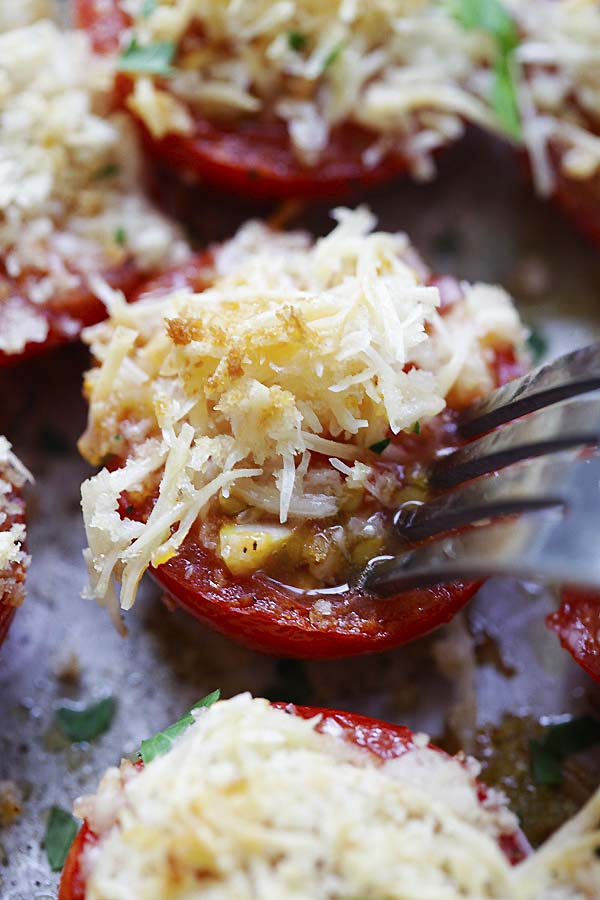 Close-up of garlic parmesan baked tomatoes poked with a fork.