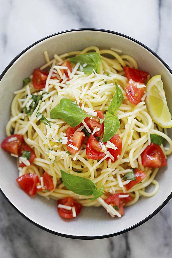 Healthy and delicious spaghetti pasta with tomatoes, fresh basil, Parmesan cheese and lemon sauce.