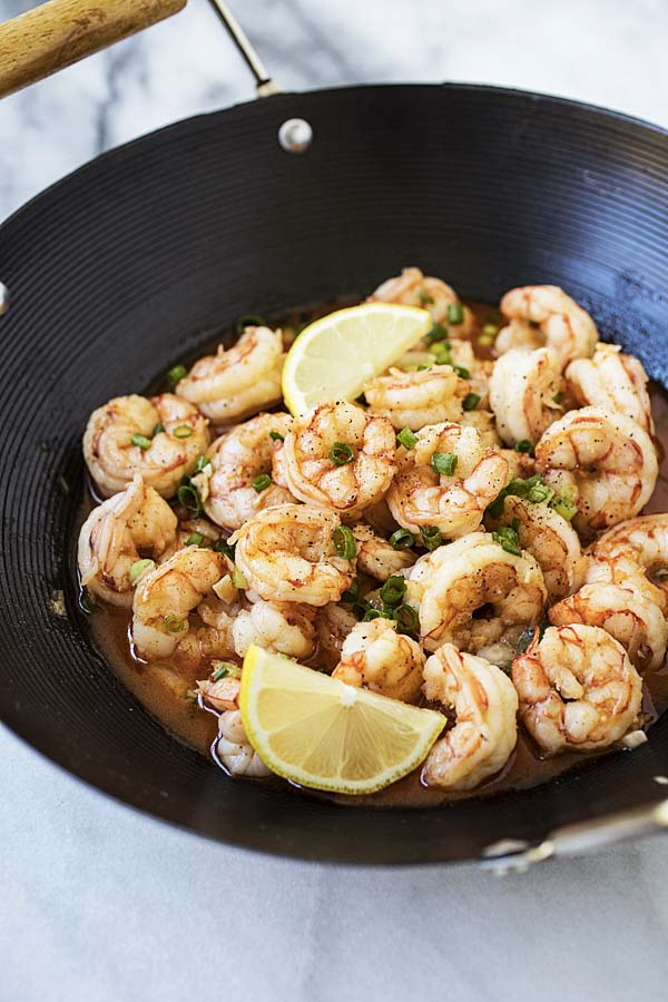 Asian garlic butter shrimp topped with lemon wedges.