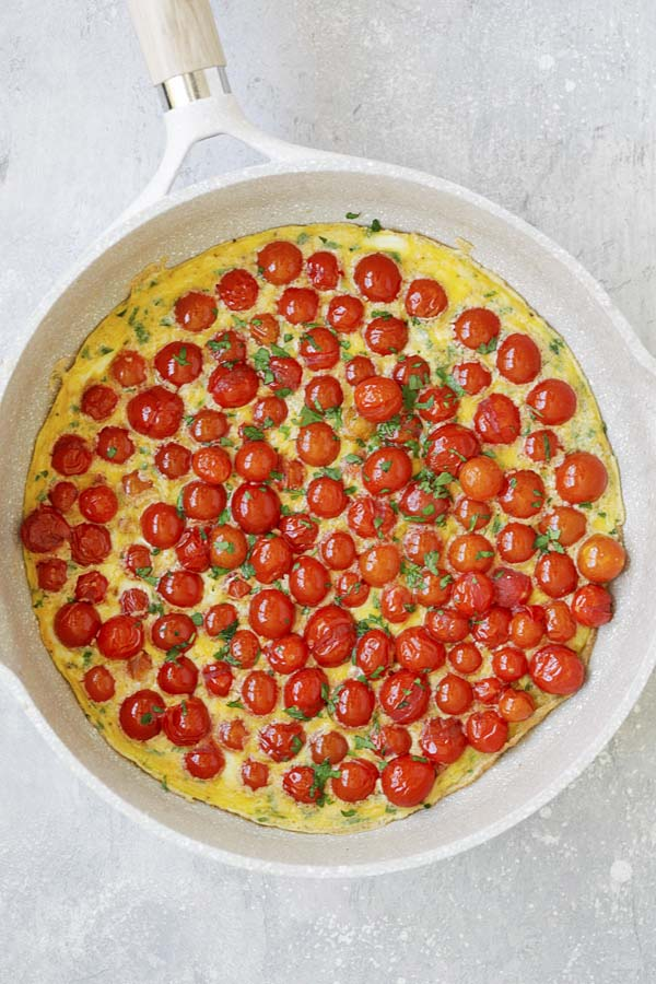 Easy and quick cherry tomato Italian frittata in a skillet.