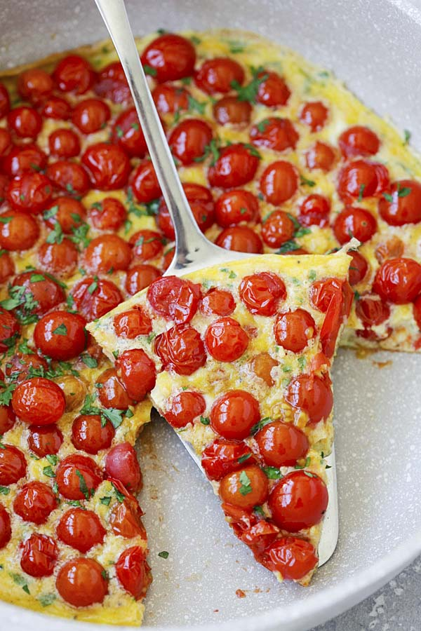 A slice of delicious cherry tomato frittata in a skillet.