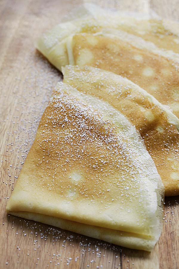 Folded crepes pancakes dusted with powdered sugar.