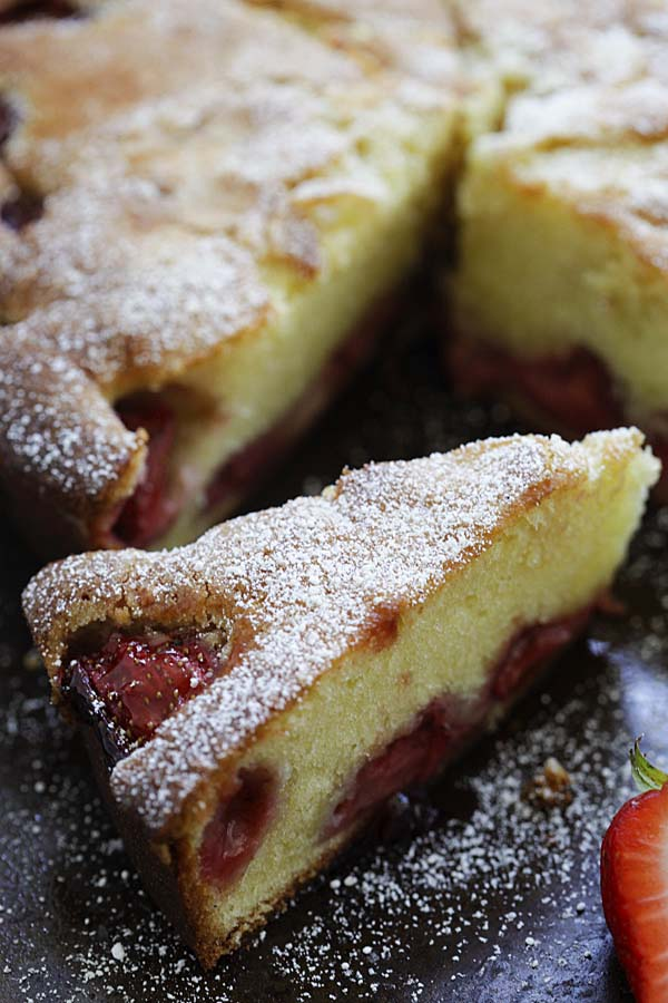 A slice of homemade delicious strawberry cake topped with powdered sugar.