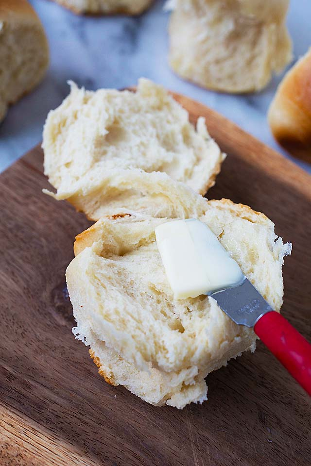Spreading butter on a super soft homemade dinner roll.