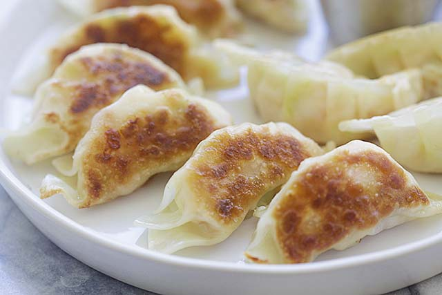Golden pan-fried shrimp potstickers with a pair of chopsticks on a white plate.