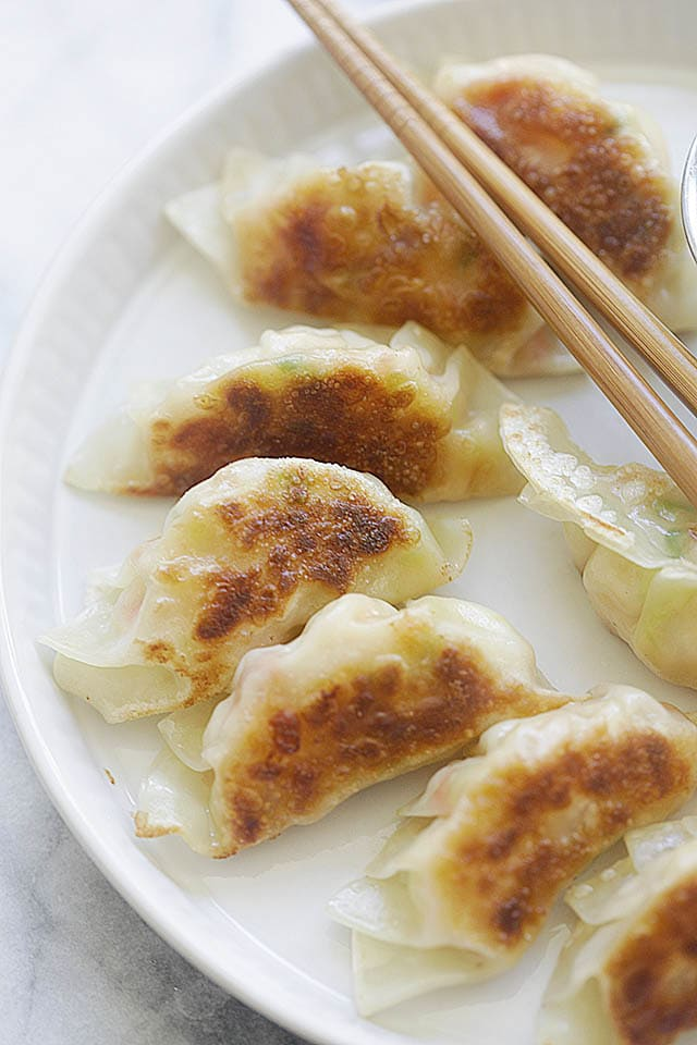 Potstickers on a serving platter with dipping sauce.