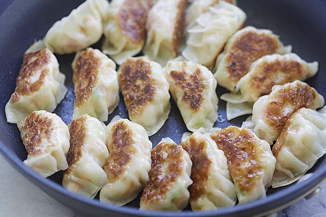 Pan-frying potstickers on a non-stick pan.