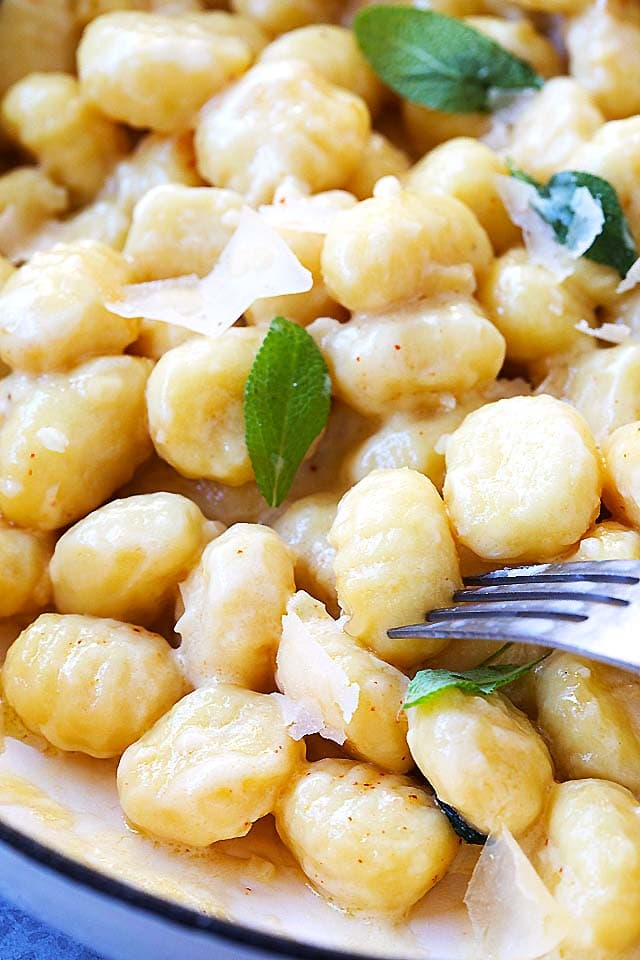 Soft and creamy potato gnocchi in garlic sauce, topped with shaved Parmesan cheese, ready to be served.