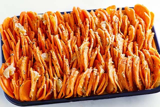 Raw slices of sweet potato chips on a baking tray.