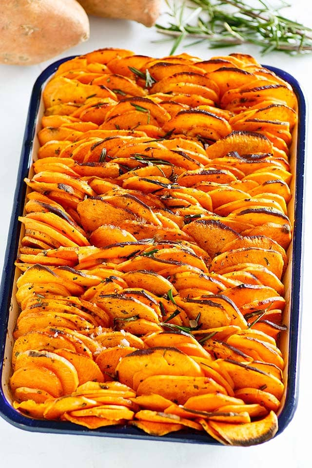 Thinly sliced and roasted sweet potatoes nicely stacked on a baking tray, ready to be served.